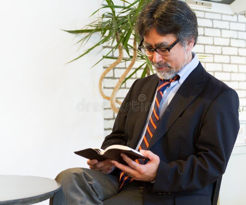 Japoński biznesowy mężczyzna w kostium czytelniczej książce z winem, relaksuje w krześle obraz stock