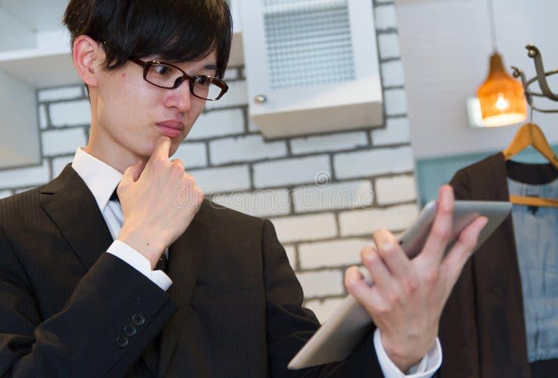 Japoński biznesowy mężczyzna w kostiumu, myśleć nowego plan, ogląda pastylka przyrząd zdjęcia royalty free