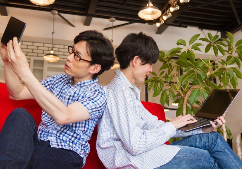 Japoński brat używa pastylka laptop i przyrząd w żywym pokoju zdjęcie royalty free