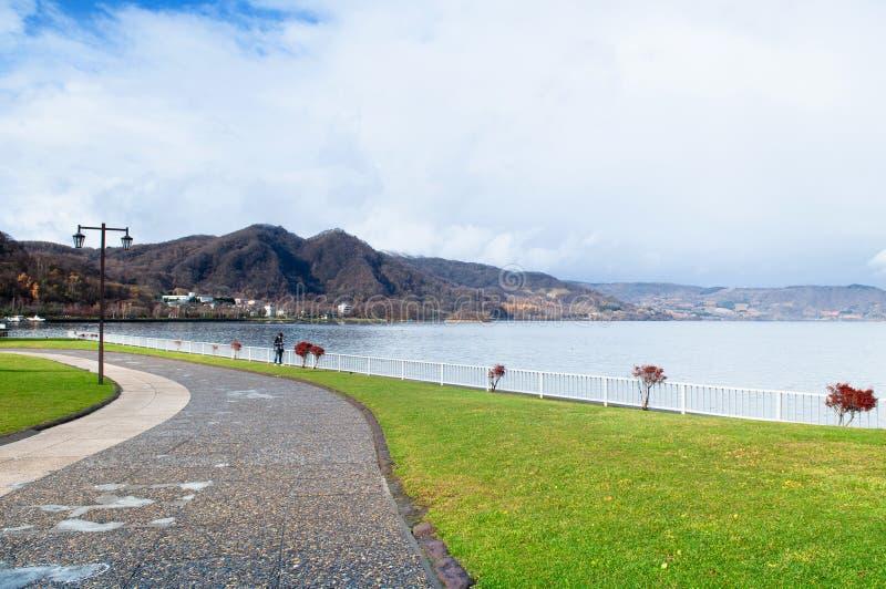 Japoński mężczyzna spacer wzdłuż jeziornego Toya brzeg na jasnych niebo zimy morzach obrazy stock