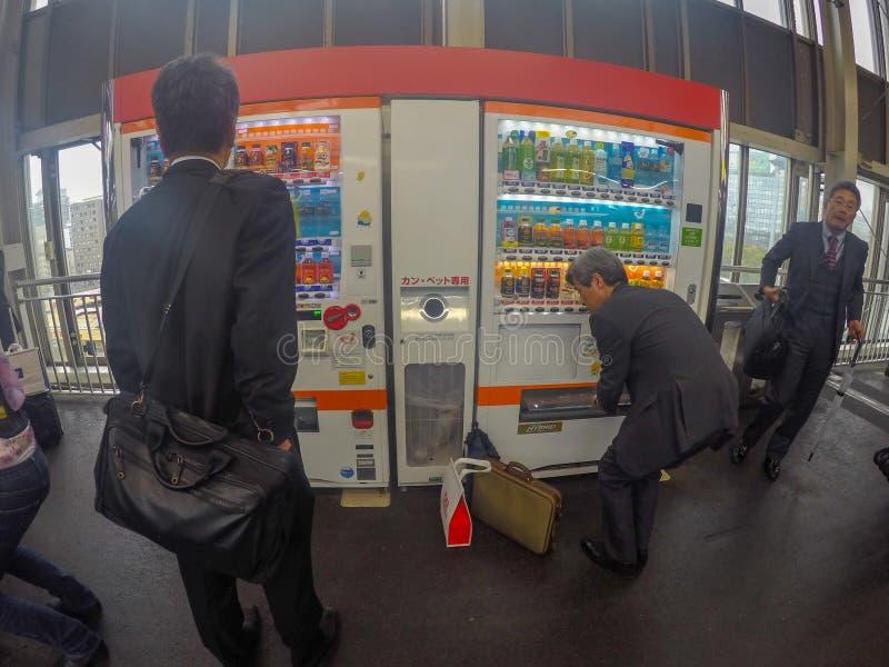 Japoński pensyjny mężczyzna podnosi jego napój up od pić vending m zdjęcia royalty free