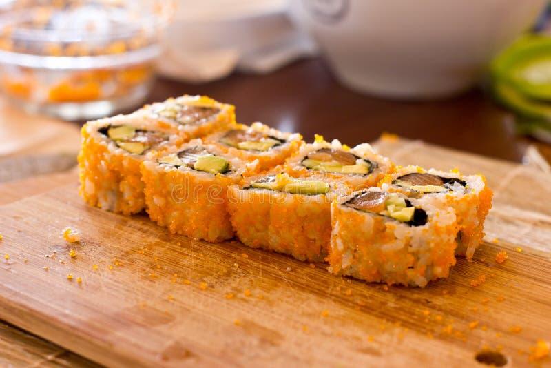 Japoński suszi i rolki z łososiem, avocado, ogórkiem i flyi, obraz royalty free
