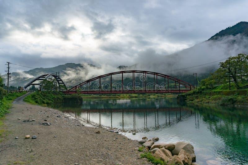 Japoński wieś krajobraz z dwa mostami nad rzeką obrazy stock