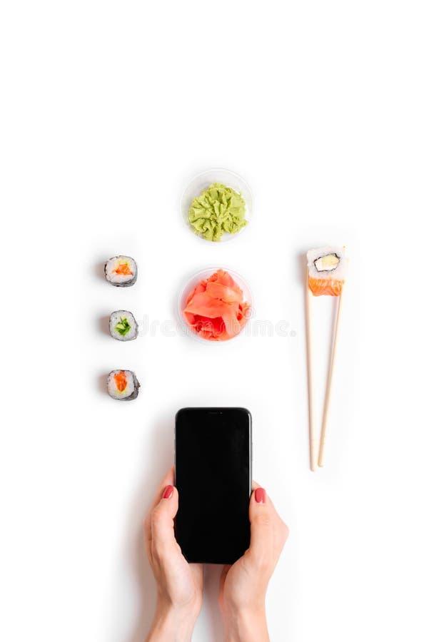 Japońskiej restauracji dostawy i rozkazu suszi rolek chopsticks online ręki trzyma odgórnego telefonu mockup bielu tło zdjęcie royalty free