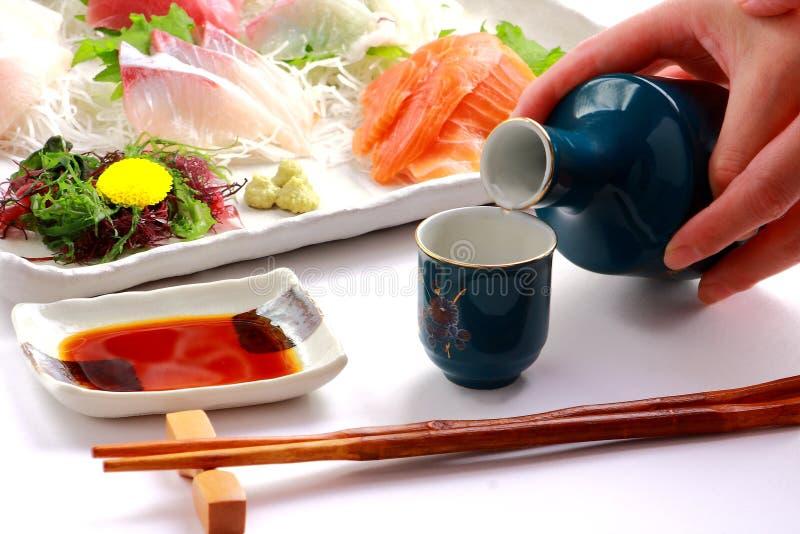 ` Japonés del MOTIVO del ` del vino de arroz y ` del Sashimi del ` crudos de los pescados imagen de archivo libre de regalías