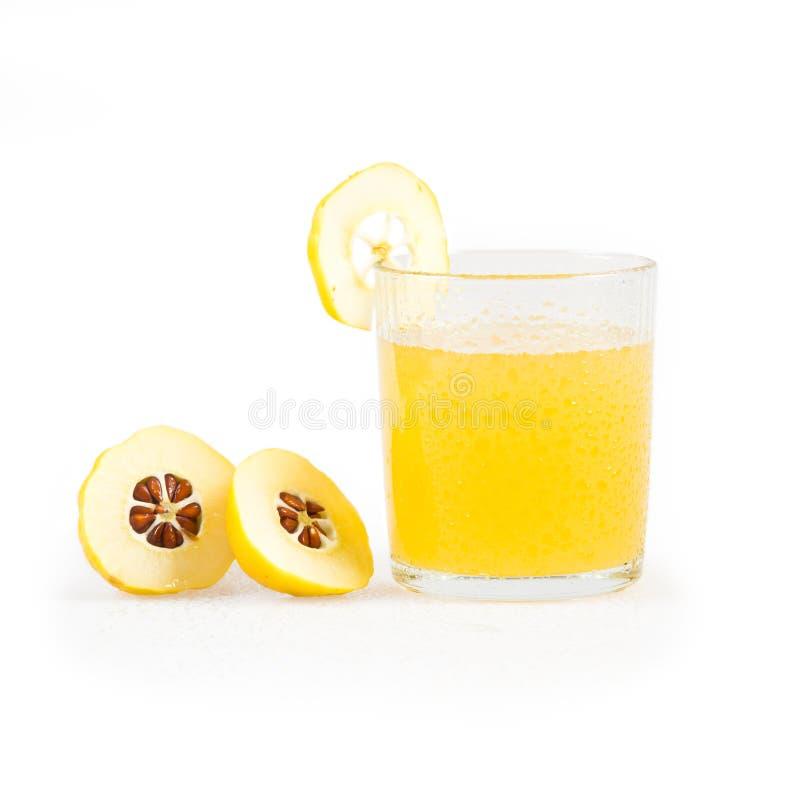 Japonica Chaenomeles Ιαπωνικός ανθίζοντας χυμός κυδωνιών στο γυαλί και φρούτα με τα σταγονίδια νερού στοκ εικόνα
