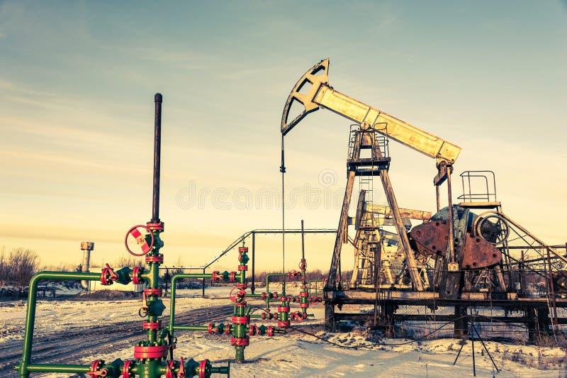 Jaque e fonte da bomba de ?leo em um campo petrol?fero Minera??o e setor petroleiro Conceito da produ??o de eletricidade imagens de stock