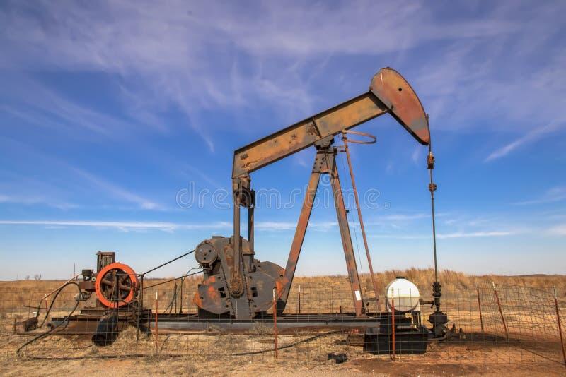 Jaque oxidado velho da bomba de poço de petróleo que senta-se no campo com o céu dramático azul brilhante - cabeça de olhares da  imagens de stock