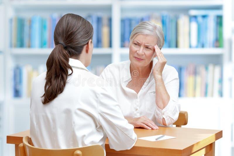 Jaqueca paciente mayor del dolor de cabeza del doctor foto de archivo