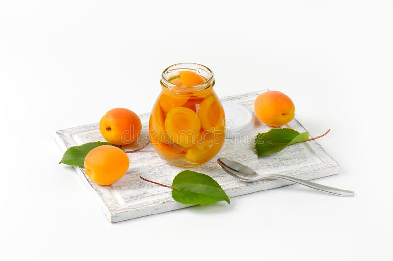 Jar of apricot compote. And bowl of fresh apricots stock photos
