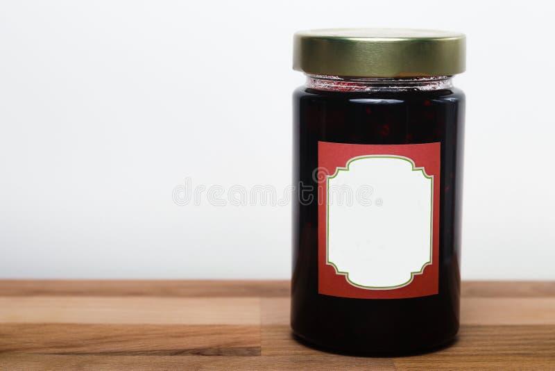 Jar av fruktsylt på träbordet omgiven av vit bakgrund royaltyfri foto