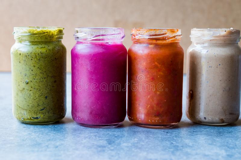 Jar of Beet Dip Sauce, Almond Butter or Tahini Pistachio Urbech and Salsa Tomato Paste Sauce stock photography