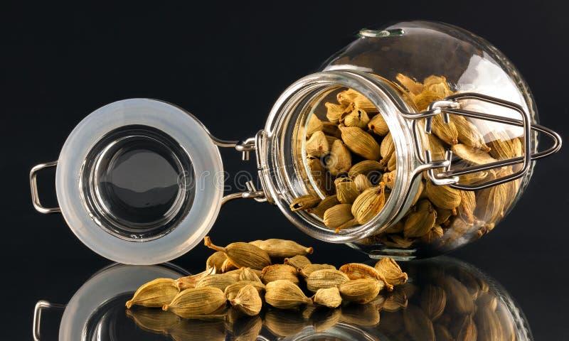 Jar of cardamom pods. Open jar with spilling cardamom pods on black reflective surface stock image