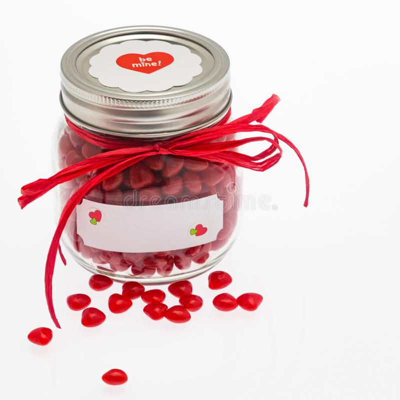 Jar of cinnamon hearts for Valentine`s Day. royalty free stock image