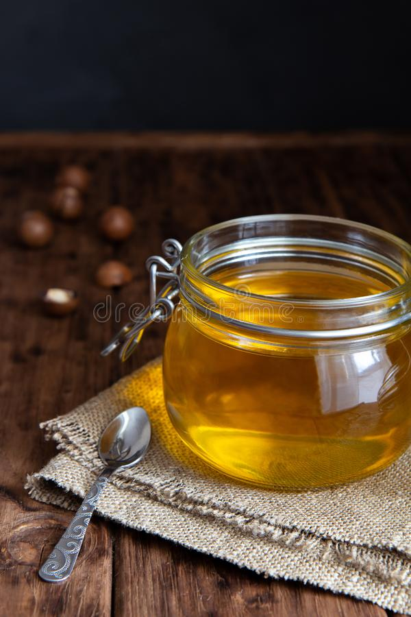 Jar of clarified ghee butter on a wooden table on a black background. Jar of clarified ghee butter on a wooden table. Burlap, macadamia nuts. Country style stock photography