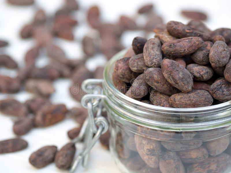A jar of cocoa beans. Cocoa beans in a jar, selective focus royalty free stock photos
