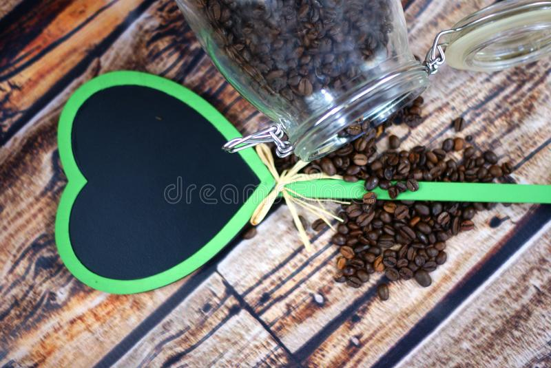 Jar of coffe beans and heart of blackboard. stock image