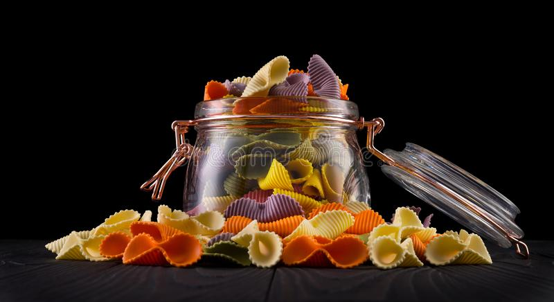 Jar of colorful farfalle pasta on wooden table isolated on black background royalty free stock photo