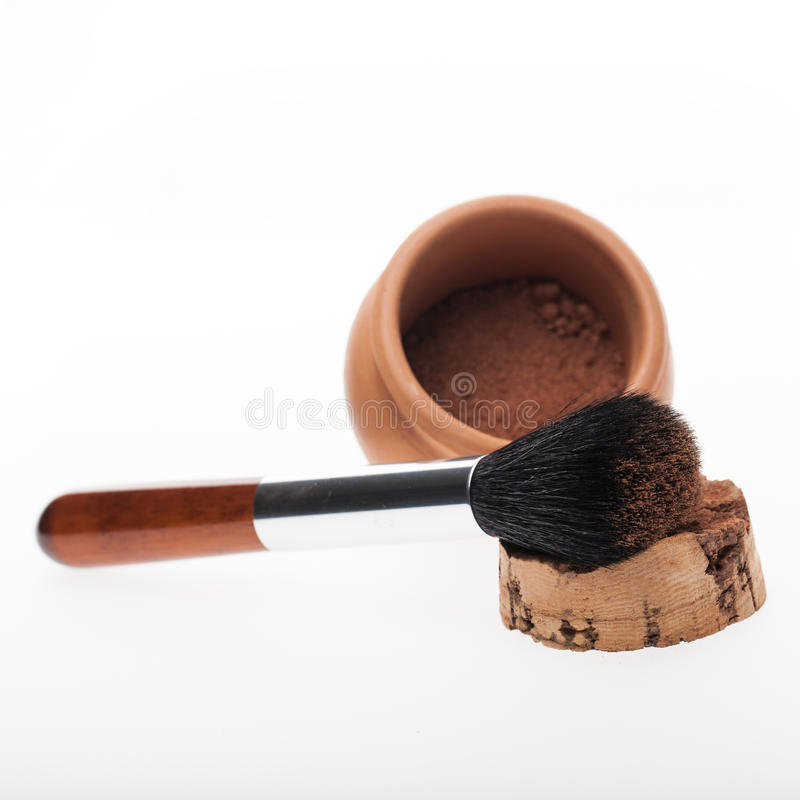 Jar of cosmetic powder. Open jar of cosmetic powder with the cork removed and a large soft bristle brush or applicator for contouring it onto the skin in a stock photos
