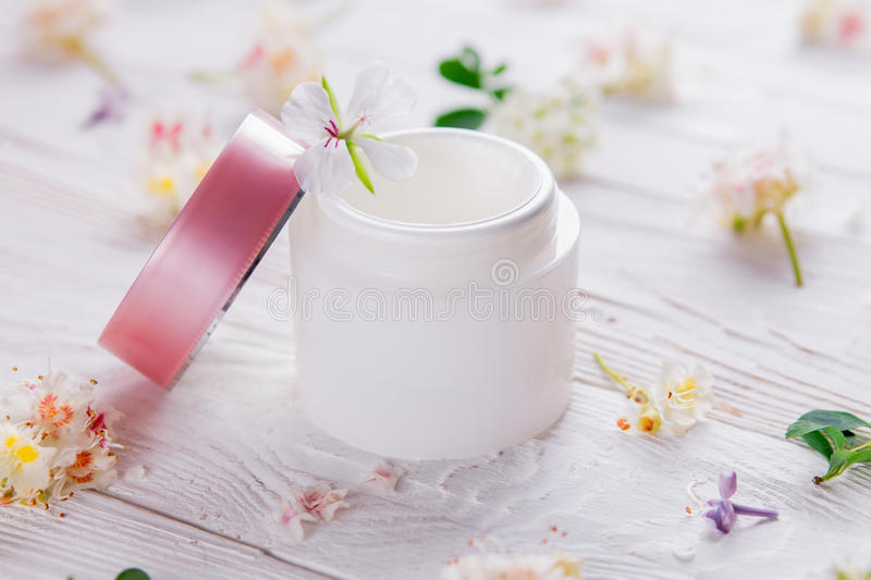 Jar with cream surrounded with flowers stock images
