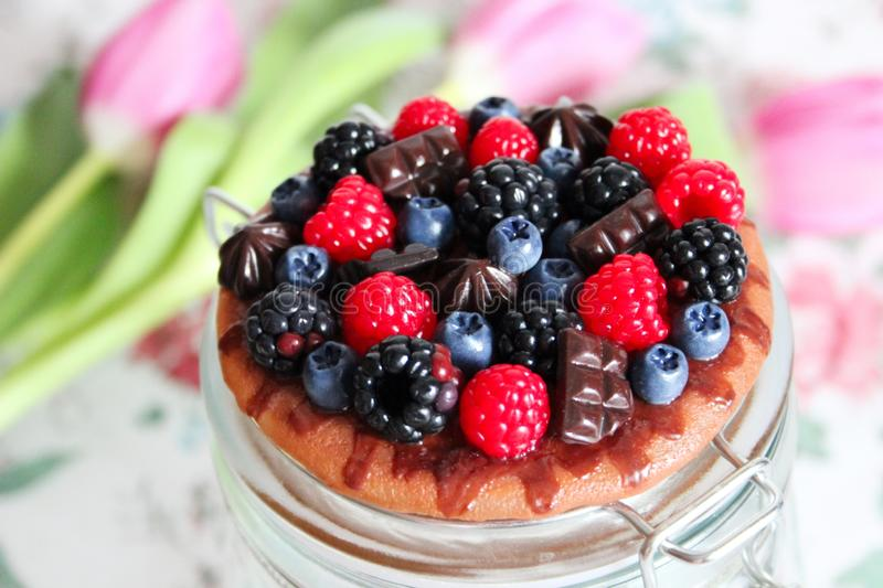 Jar decorated with berries and chocolate. stock image