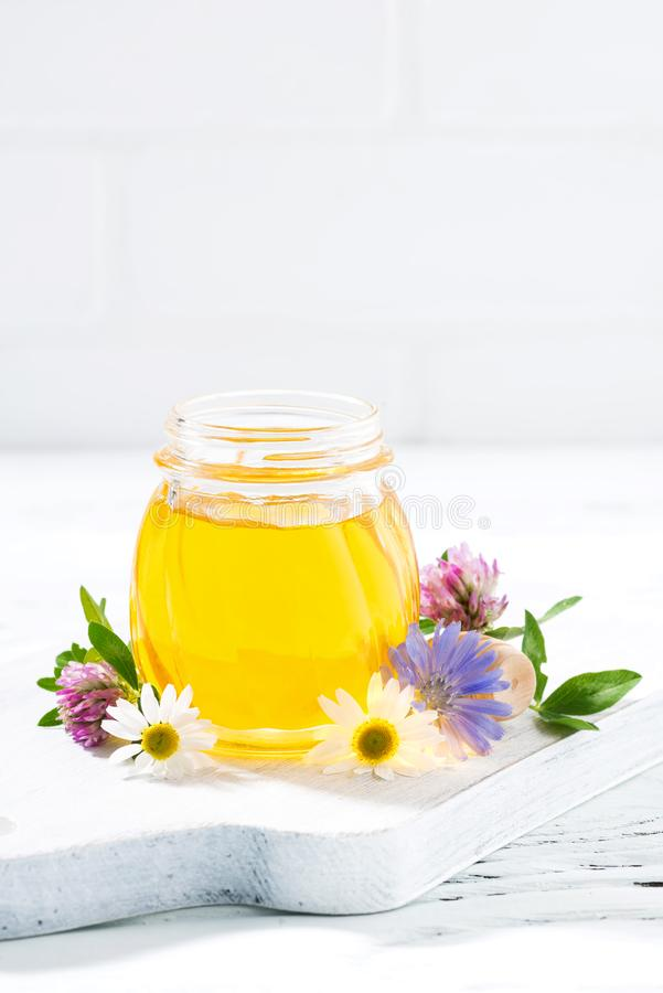 Jar with fresh flower honey and white background, vertical. Closeup royalty free stock image