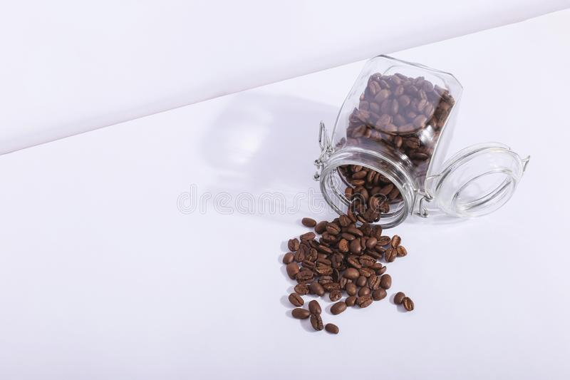 A jar of fresh fragrant coffee beans, on a white background. Hard shadow from the sun, art concept of morning and energy charge royalty free stock photos