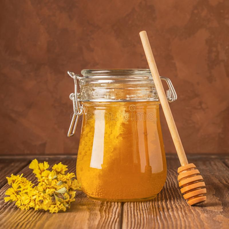 A jar of fresh golden honey and honey spoon on a wooden background on the table. The concept of natural products. stock photos