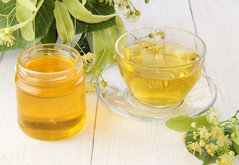 Jar of fresh sweet linden honey, cup of tea on wooden table and linden flowers stock photography