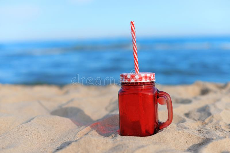 Jar glass with a cocktail drink red on the beach on the sand on the beach with the text summer written on vacation stock images
