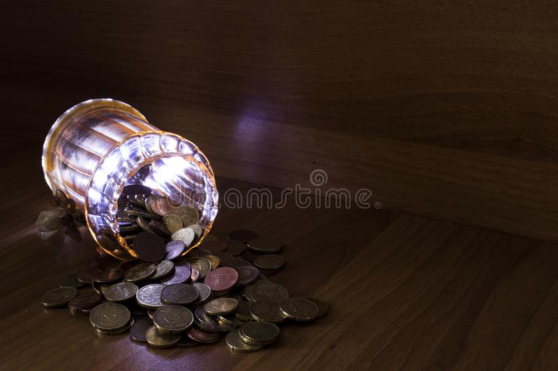 Jar of glass full of euro coins on a table using light painting stock images