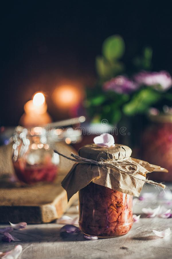 A jar with gourmet rose jam on the candle light background with roses and petals stock photo
