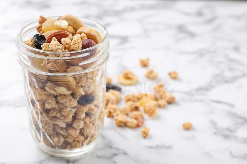 Jar with healthy granola on white marble table. Space for text royalty free stock photography