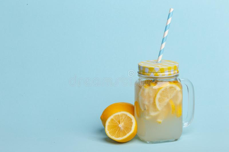 A jar of homemade lemonade and lemons on a blue background stock image