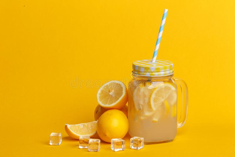A jar of homemade lemonade and lemons on a yellow background stock photo