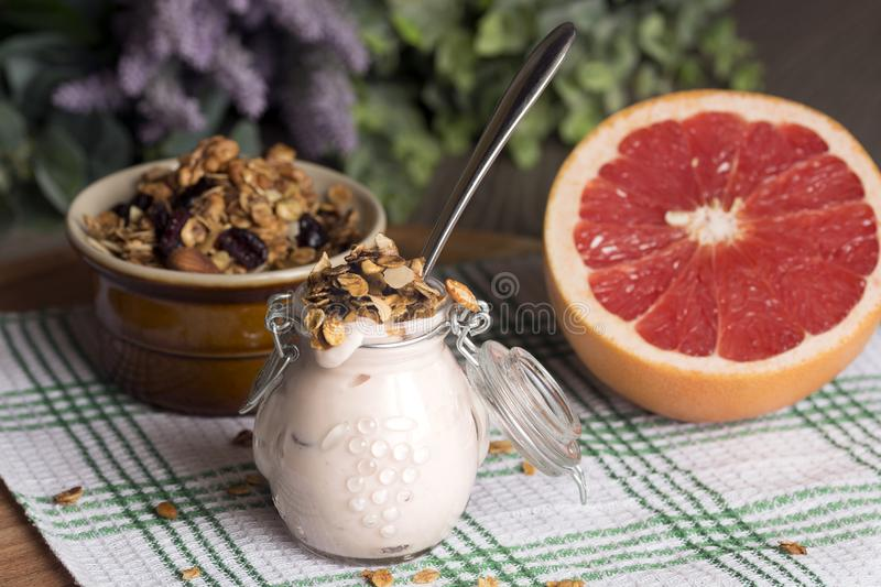 Jar with homemade yogurt. Granola from several types of cereals with nuts, coconut shavings and dried cranberries. and grapefruit.  stock photos