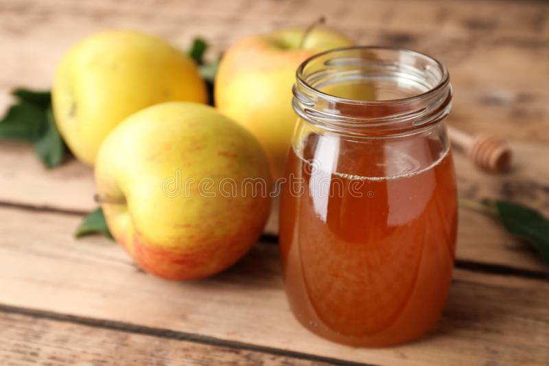 Jar of honey and apples on table. Jar of honey and apples on wooden table royalty free stock images