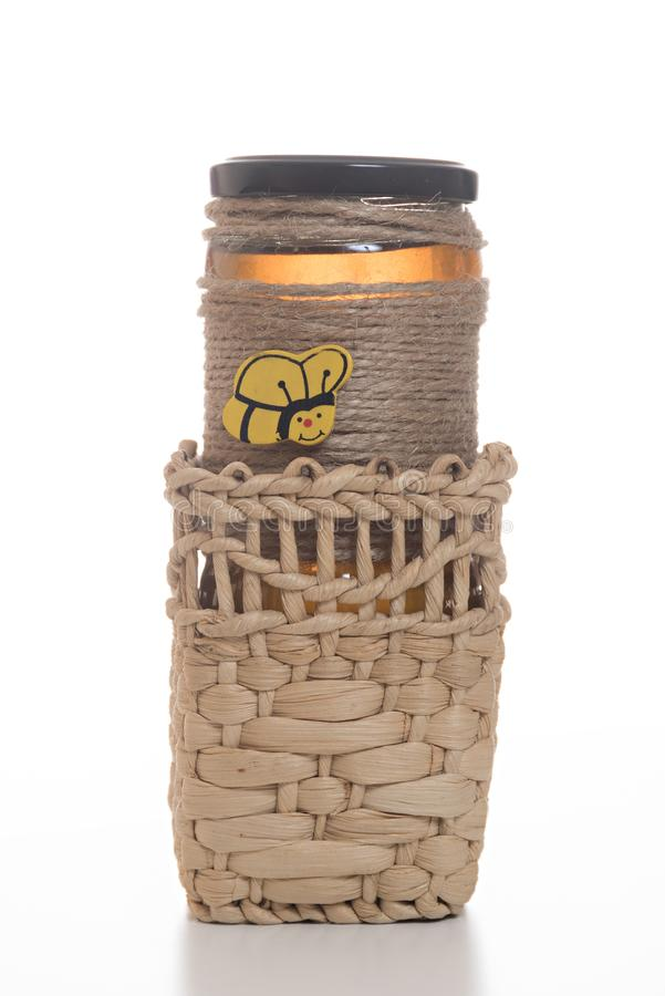 Jar of honey in a basket royalty free stock image