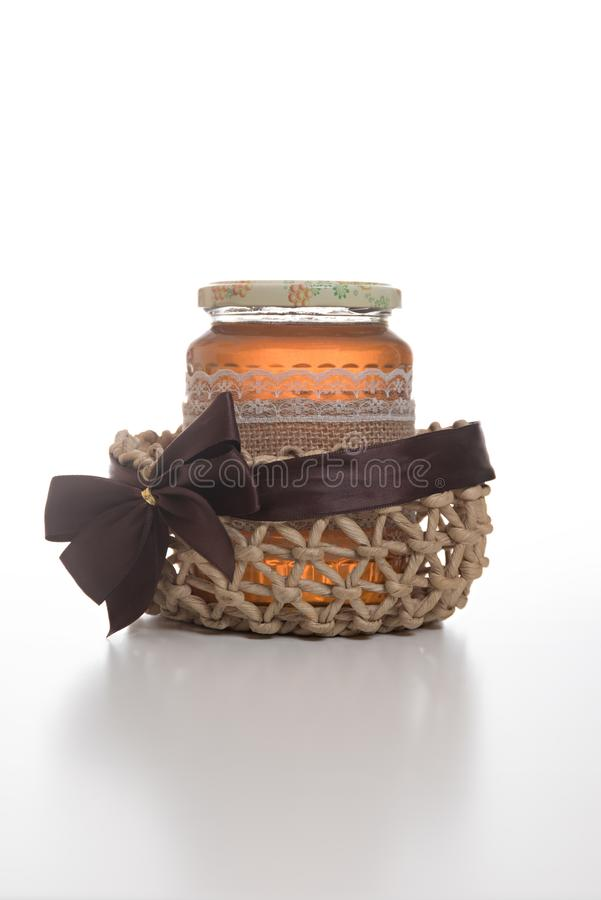 Jar of honey in a basket royalty free stock images