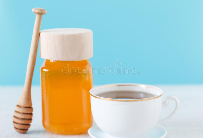 Jar of honey and a cup of tea stock photo