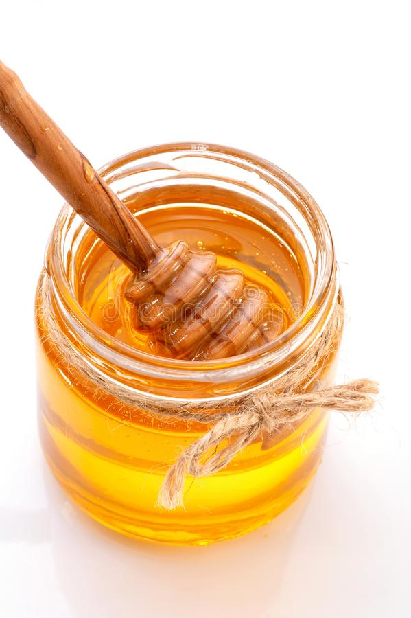 Jar of honey with honey dipper  inside close-up on white background. Decorated with bow of twine royalty free stock image