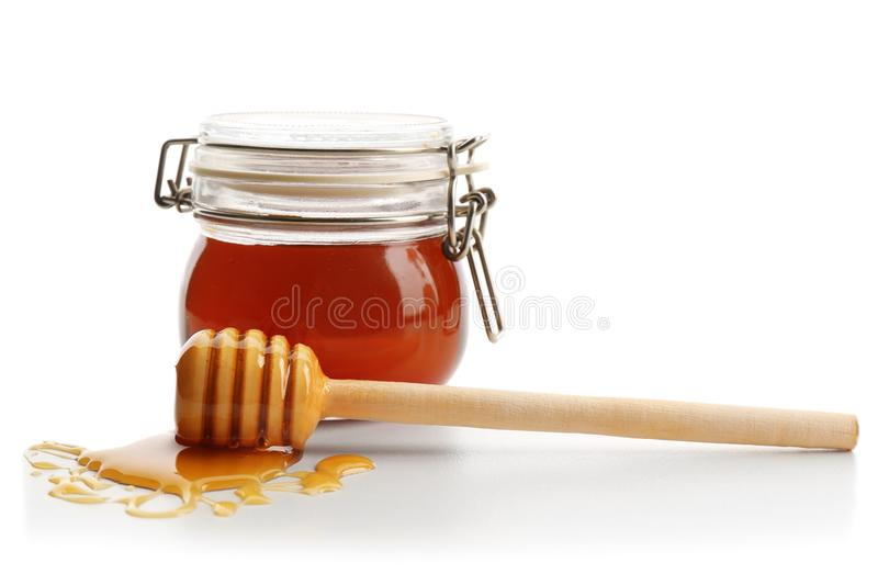 Jar of honey with dipper, isolated. On white stock photos