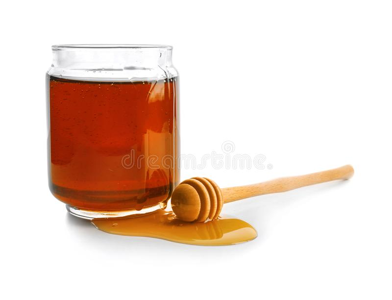 Jar of honey with dipper,. On white royalty free stock image