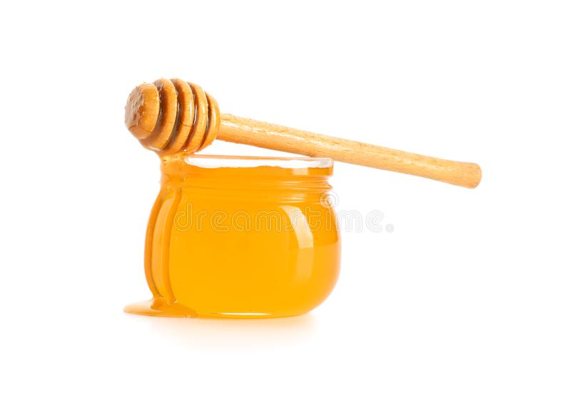 Jar of honey with dipper on white background stock photo