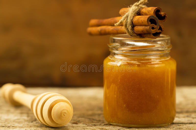 Jar of honey with drizzler and cinnamon on wooden background. Small jar of honey with drizzler and cinnamon on wooden background stock images