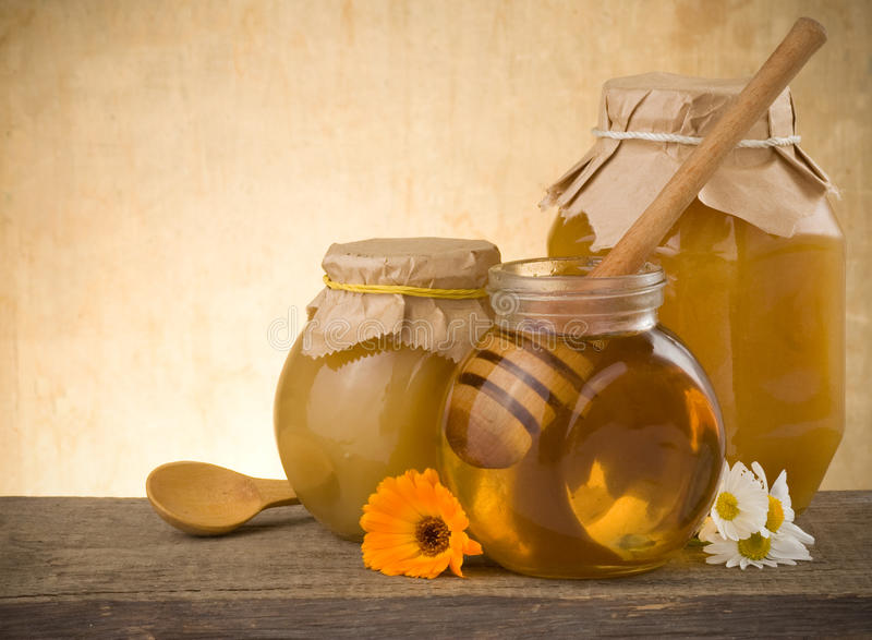 Jar of honey and flowers on wood. Background royalty free stock photo