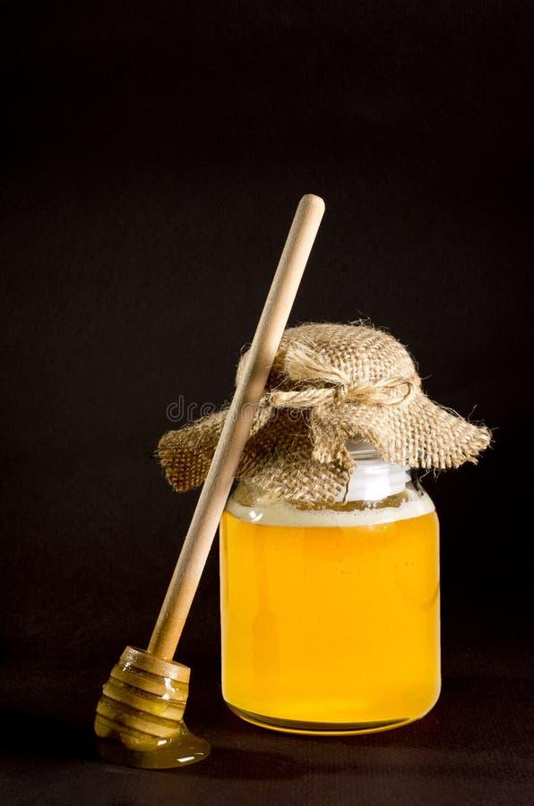 Jar of honey with honey scoop stock photo