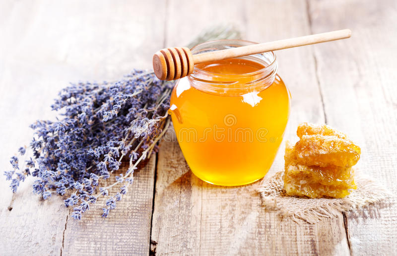 Jar of honey with honeycomb and lavander flowers royalty free stock image