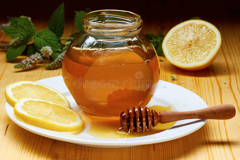 Jar of honey over white plate with dripper, lemon slices and flowering mint. On wooden table. Rustic style stock photography