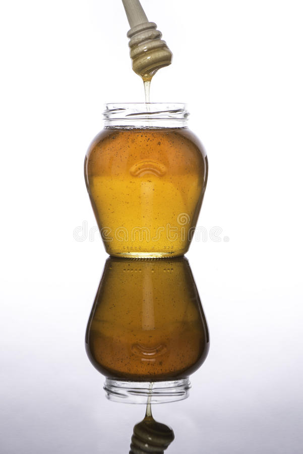 Jar of honey reflected with dipper royalty free stock images